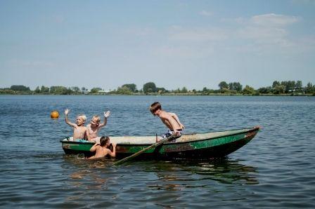 Kinderen in een roeiboot op het meer